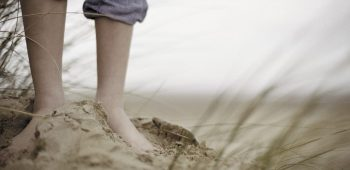 Boy Standing Barefoot in Sand